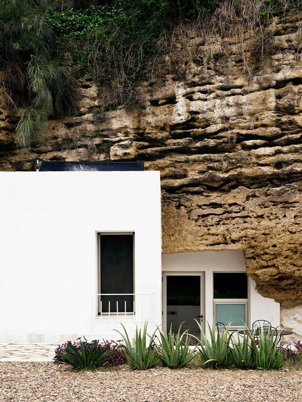 Modern white boxes combine with ancient cave to create an artists home