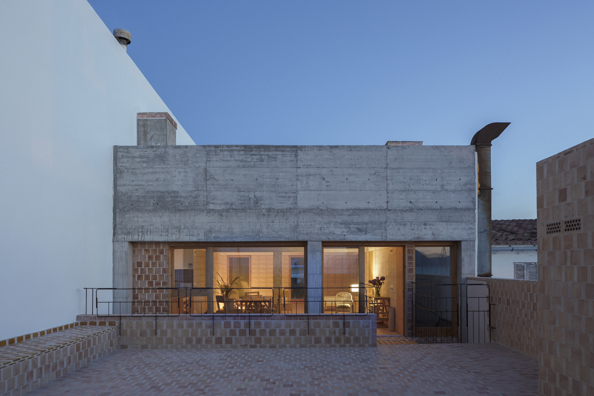 Modern home at night with a mixture of exposed concrete and terracotta tiles