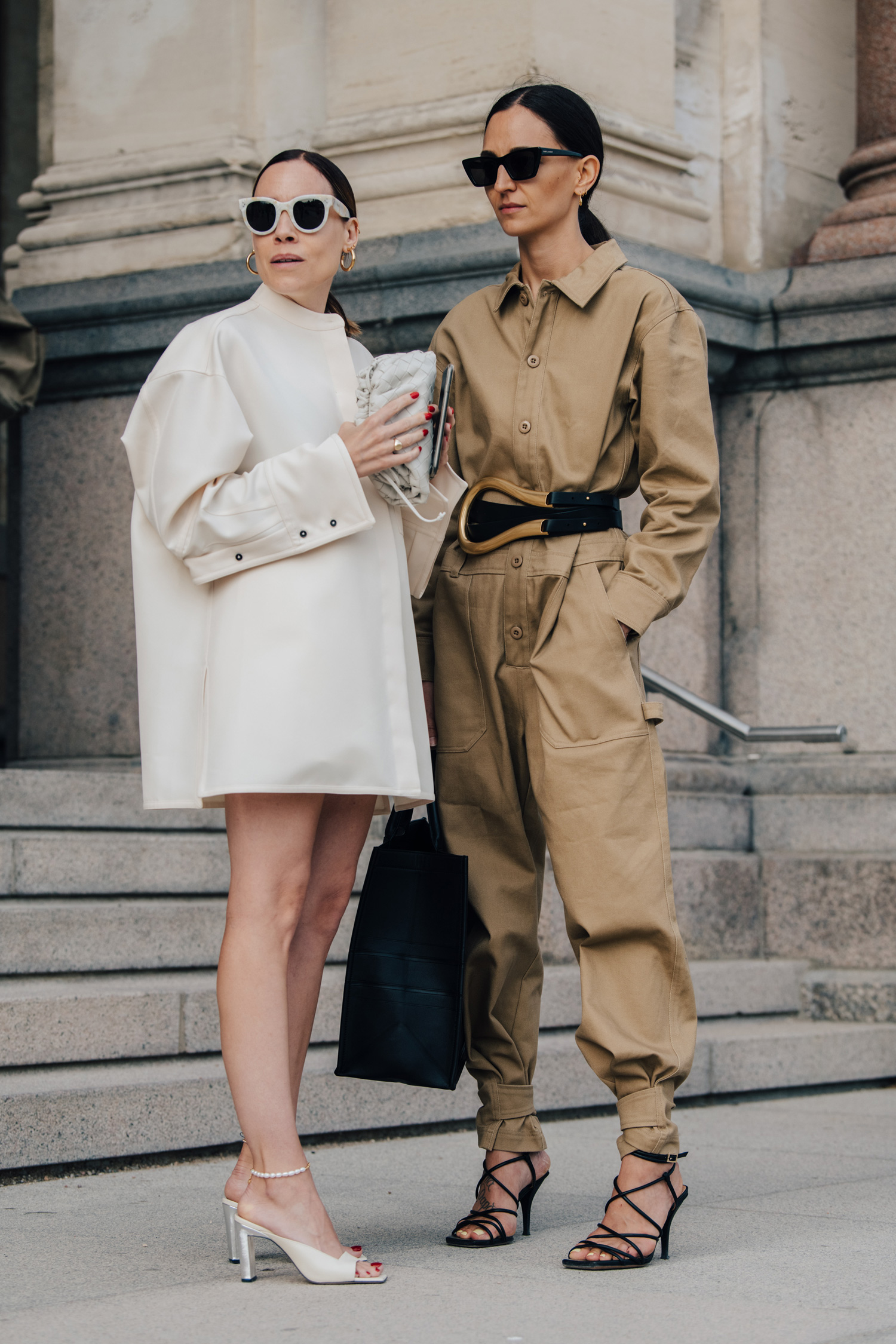 Two women snapped in stylish goats and overalls